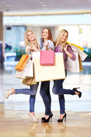 Three beautiful girls with shopping bags in shop Stock Photo - 13709407