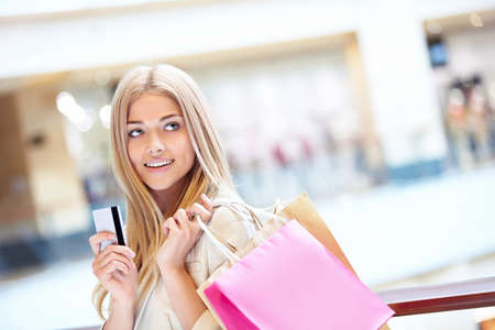 debit card: Beautiful girl with shopping bags and credit card
