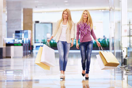 Beautiful girls with shopping bags walking in the store Stock Photo - 13936955