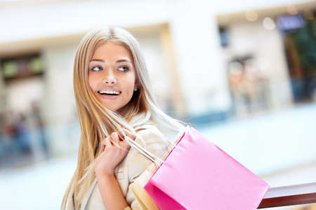 shopping bag: Smiling girl with shopping bags in shop Stock Photo
