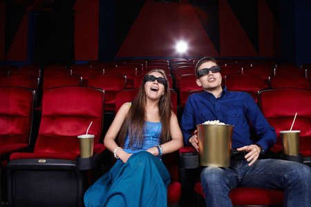 Surprised young couple in a movie theater photo