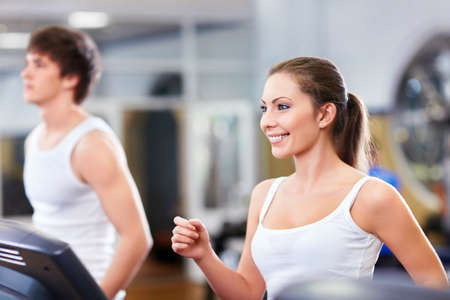 Smiling people on treadmills at fitness club photo