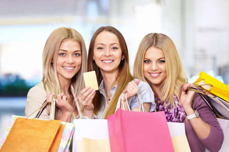 Young attractive girls with shopping bags and credit card photo