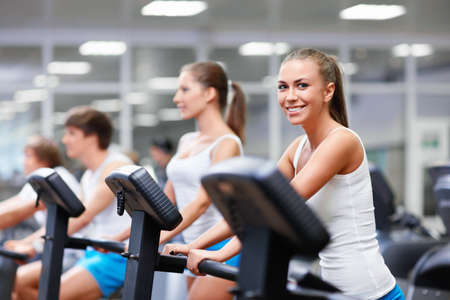 Smiling young people on treadmills photo