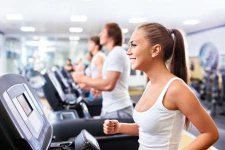 Smiling people on treadmills photo