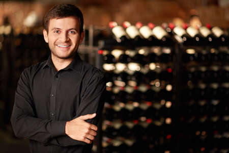 Sommelier of rack with bottles of wine