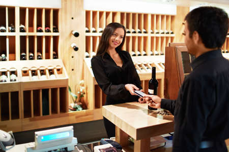 cashier: Man buys a bottle of wine in the store Stock Photo