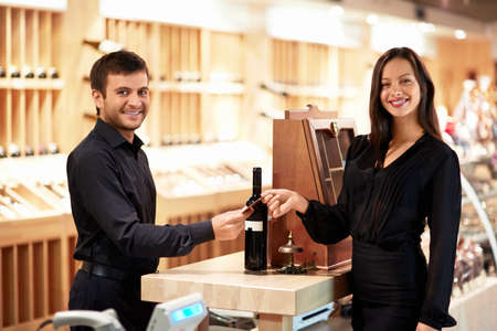 Woman buys a bottle of wine in the store photo
