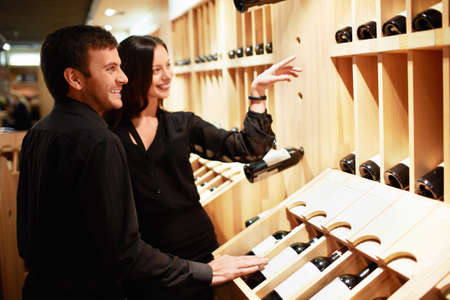 wine store: Young couple chooses the wine