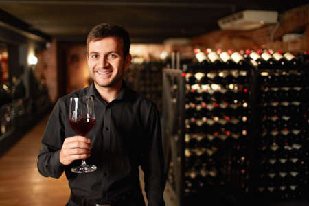 degustation: Man with a glass of wine in the cellar
