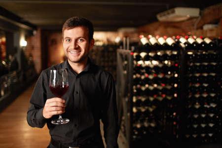 Mann mit einem Glas Wein im Keller Standard-Bild