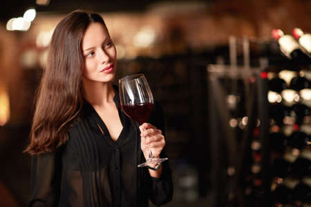 Young girl with a glass of wine in the cellar photo