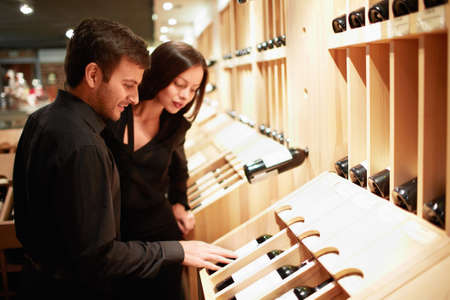 supermarket shelves: Young couple choosing wine in a store Stock Photo