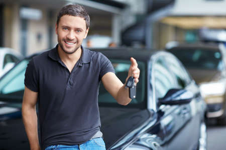 selling service smile: Young man with the keys at the car
