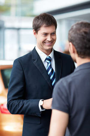 selling service smile: Young man with a salesman in a motor show