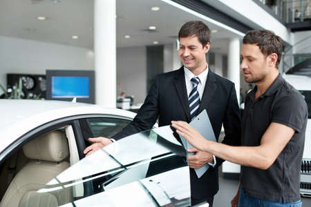 automobile dealership: Young man with a salesman in a motor show