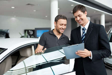 selling service: Young man with a salesman in a motor show