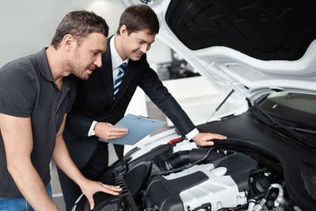 Young man with a salesman in a motor show Stock Photo - 15501851