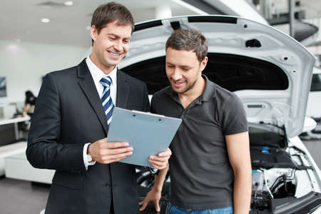 selling service smile: The seller and the buyer in the auto show Stock Photo