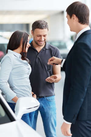 Seller gives the keys a couple in the showroom photo