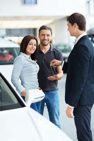 Seller gives the keys a couple in the showroom Stock Photo - 15573193