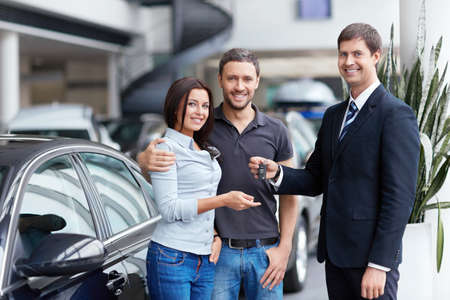 selling service smile: Seller and a couple of with the keys to car Stock Photo