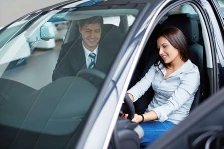 Woman in the car and seller at a showroom photo