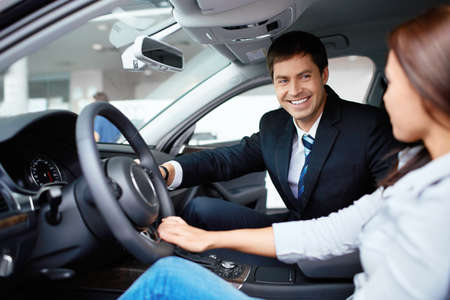 car sales: Woman in the car and seller at a showroom