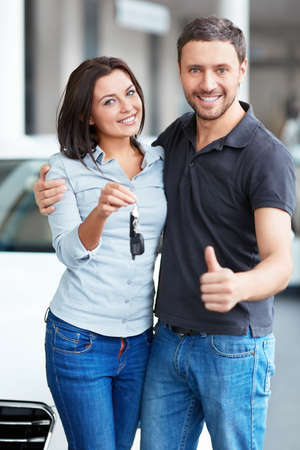automobile dealership: Young couple with car keys