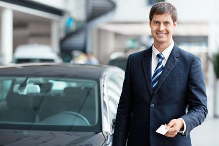 automobile sales: Seller with a business card in the showroom