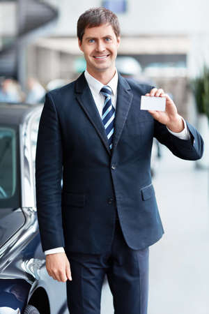 Seller with a business card in the showroom Stock Photo - 15573202