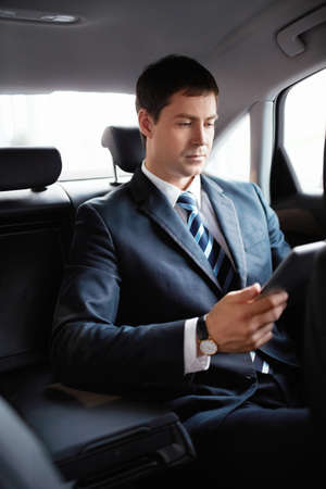 Businessman in the car with the tablet Stock Photo - 15573157