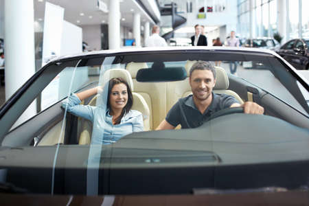 selling service smile: Young couple in a cabriolet in the showroom