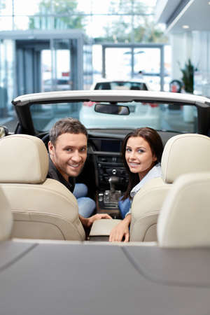 automobile dealership: Young couple in a cabriolet in the showroom