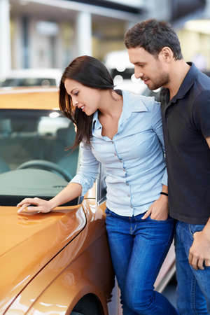 buying a car: Attractive couple chooses a car