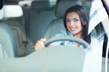 selling service smile: Beautiful girl at the wheel a car