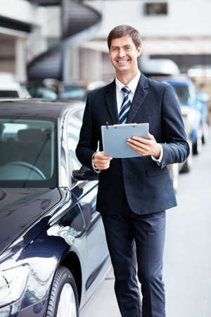 selling service smile: Man in suit at the car Stock Photo
