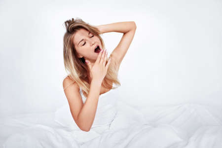yawning: Young girl yawning in bed