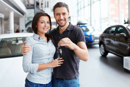 selling service smile: Young couple with car keys