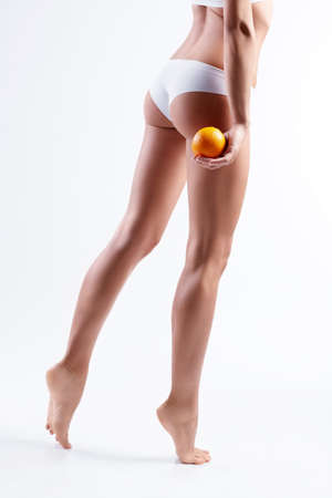Female hips with orange on white background photo