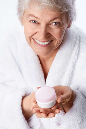 one senior woman only: Elderly woman with cream on a white background