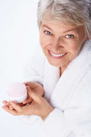 Elderly woman with cream on a white background photo
