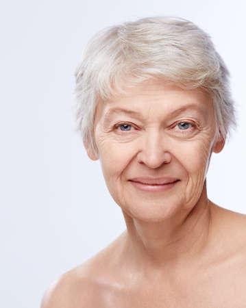 mujeres maduras: La mujer mayor en el fondo blanco Foto de archivo