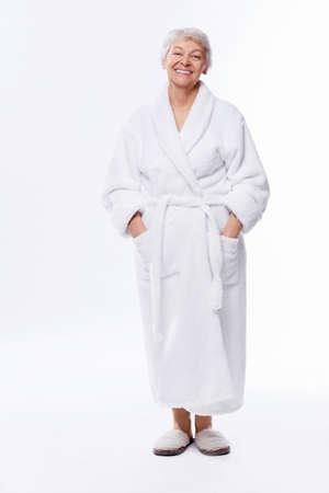 Ältere Frau im Bademantel auf weißem Hintergrund