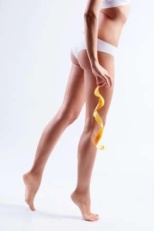Women Cellulite: Piernas femeninas en un fondo blanco con piel de naranja