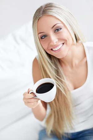 Beautiful young girl with a cup of coffee at home Stock Photo - 17446002