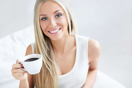 �aucasian: Beautiful young girl with a cup of coffee at home