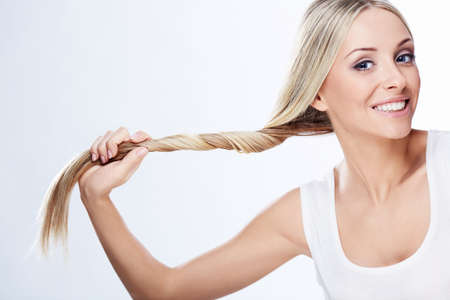 �aucasian: Beautiful young girl holding hair on a white background
