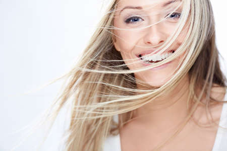 flying woman: Smiling girl with flying hair on a white background Stock Photo