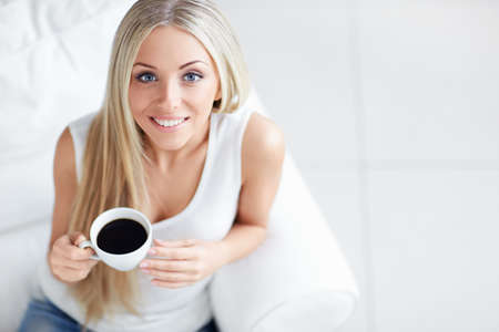 woman drinking coffee: Young beautiful girl with a cup Stock Photo